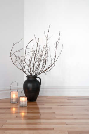 chandler: Cozy lanterns and tree branches in a vase, decorating a room