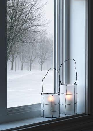 Cozy lanterns on a windowsill, with winter landscape seen through the window
