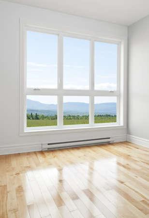 Zomer landschap gezien door het grote raam van een lege kamer