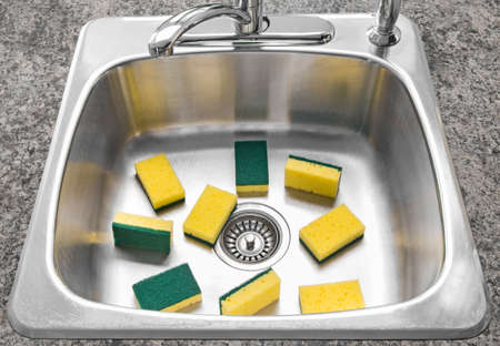 Lots of yellow and green sponges in a clean shiny kitchen sink
