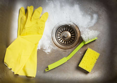 sink drain: Cleaning products and rubber gloves in a dirty kitchen sink