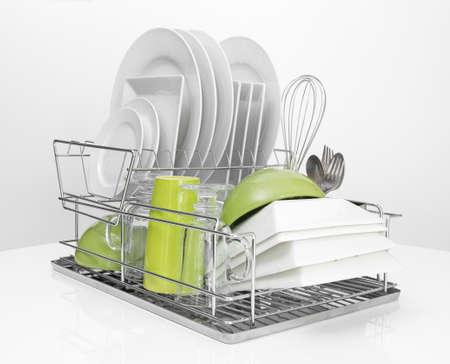 lavar platos: Platos brillantes de secado en un plato de metal estante fondo blanco