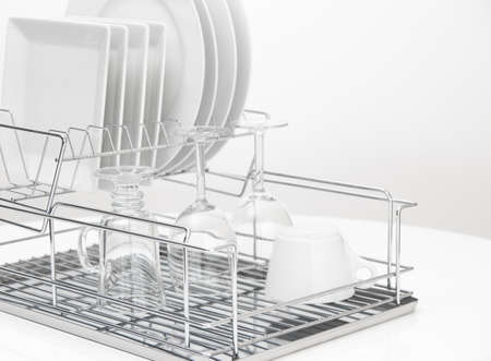 Closeup of white dishes and glasses drying on a metal dish rack  Stock Photo - 16674107