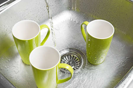Washing bright green cups in the kitchen sink  Water running from the tap  photo