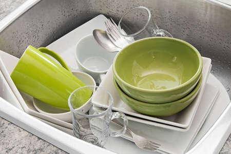 lavar platos: Lavavajillas brillantes platos en el fregadero de la cocina Foto de archivo