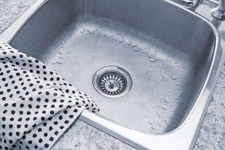 sink drain: Clean metal sink and polka dot kitchen towel  Stock Photo