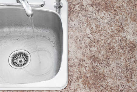 Water running from kitchen faucet  Clean new sink and countertop detail Stock Photo - 16674117