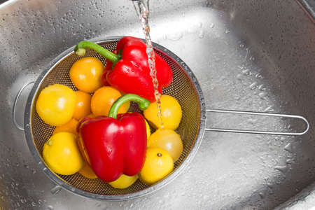 Washing colorful fruits and vegetables in the kitchen sink  photo