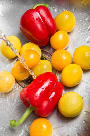 Washing red and yellow fruits and vegetables in the kitchen sink  photo