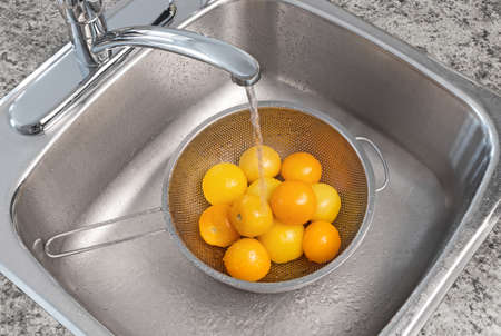 Water running from kitchen faucet  Washing yellow tomatoes  photo