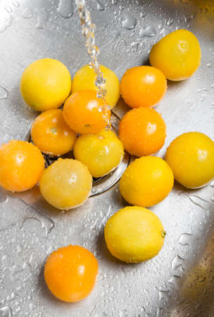 Washing yellow tomatoes and lemons in the kitchen sink  photo