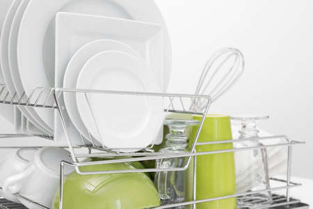 Green and white dishes drying on metal dish rack  White background Stock Photo - 16729047