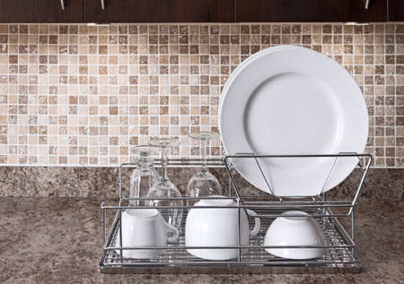 Dish rack with white plates and cups on kitchen countertop