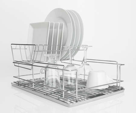 White dishes and wine glasses drying on a metal dish rack