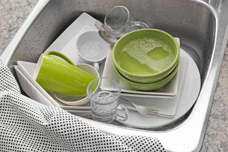 Afwassen Bright gerechten in de gootsteen en keukenhanddoek Stockfoto