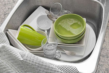 bowl sink: Dishwashing  Bright dishes in the sink and kitchen towel