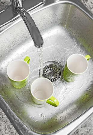 lavar platos: Lavar las tazas verdes en el agua fregadero de la cocina que va desde el grifo