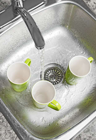 Washing green cups in the kitchen sink  Water running from the tap  photo