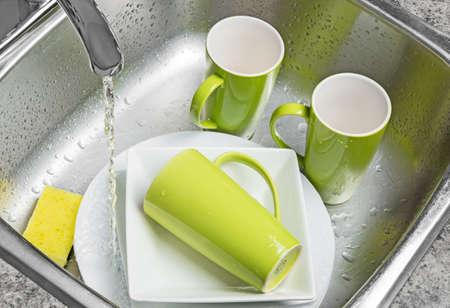 Wassen groene kopjes en witte platen in de gootsteen Water uit de kraan Stockfoto