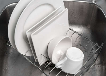 White clean dishes drying on a rack in the kitchen sink  photo