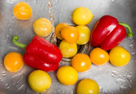 Washing bright fruits and vegetables in the kitchen sink Stock Photo - 16729054