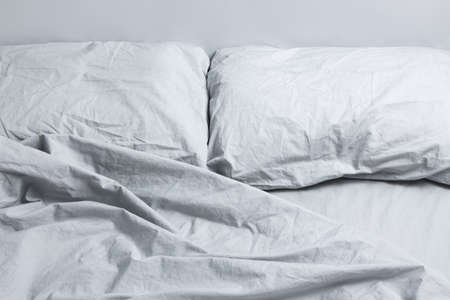 Messy bed with two pillows, gray bed linen  Stock Photo