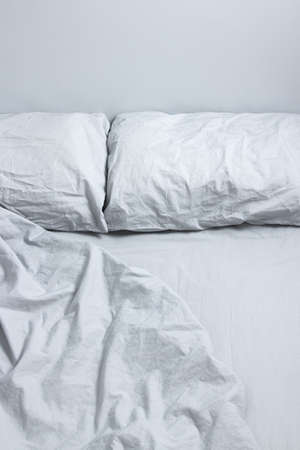 rumpled: Messy bed with two pillows and gray bedclothes