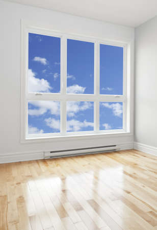 Blue sky seen through the big window of an empty room