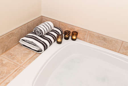 Bath with foam, fresh folded towels and candle lights  photo