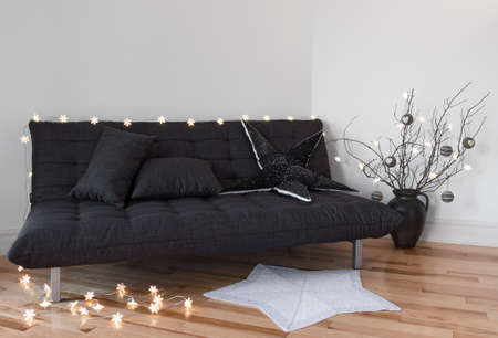 futon: Cozy lights in the living room decorating sofa and tree branches
