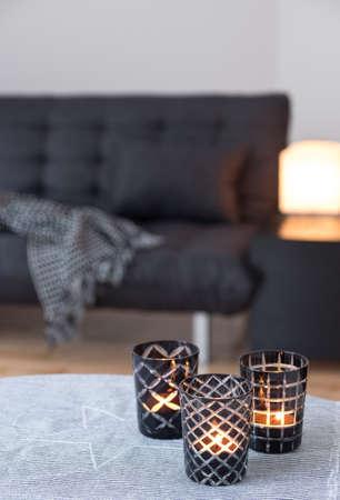 회색 소파가있는 거실을 장식 유리 캔들 홀더에 차 불빛