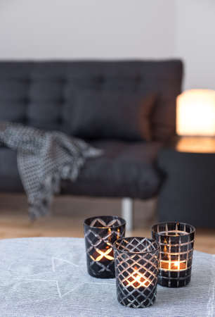 candle holder: Tea-lights in glass candle holders decorating living room with gray sofa  Stock Photo
