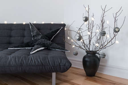 Gray sofa, winter decorations and cozy lights in the living room  版權商用圖片