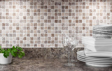 White dishware, wineglasses and green herbs on kitchen countertop  Standard-Bild