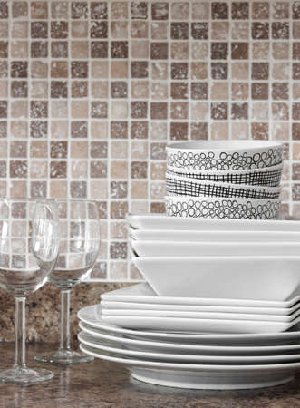 White dishes, plates and wineglasses on kitchen countertop  photo