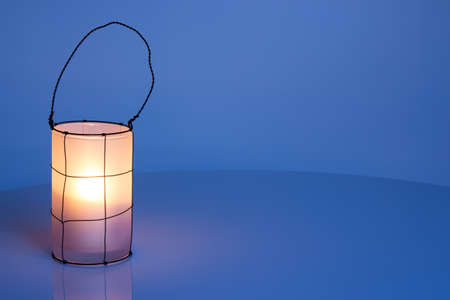 Cozy lantern on blue winter background, with copy space  photo