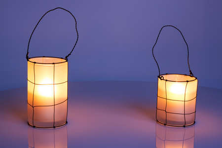 warmth: Two cozy lanterns in twilight, on colorful winter background