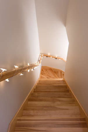 Wooden staircase decorated with cozy lights  Home interior  photo