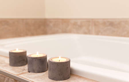 Three candles in concrete candle holders decorating bathroom. photo
