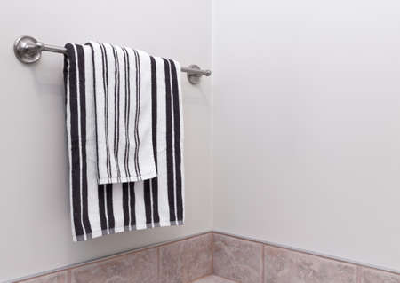 Stripped towels hanging on towel holder in the bathroom. Banco de Imagens