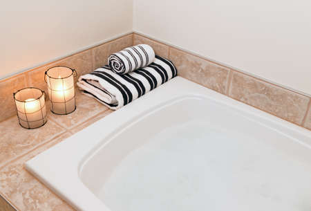 Bath with foam, fresh folded towels and cozy lanterns. photo