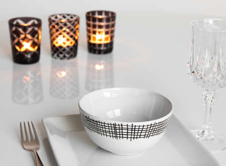 candleholders: Simple table setting with three candles in glass candleholders.
