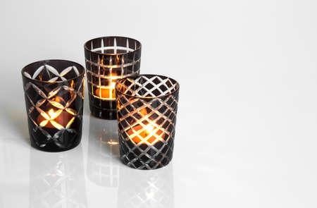 Drie theelichtjes in zwart-wit kandelaars, op het reflecterende oppervlak. Stockfoto
