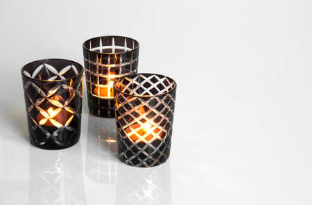 Three tealights in black and white candleholders, on reflective surface. Stock Photo