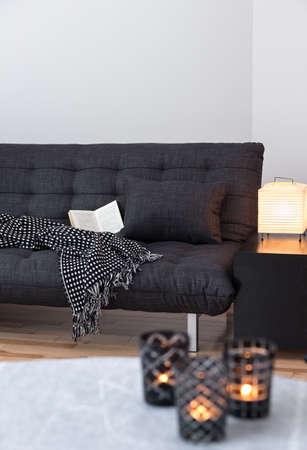 Cozy lights decorating living room with gray sofa. Standard-Bild