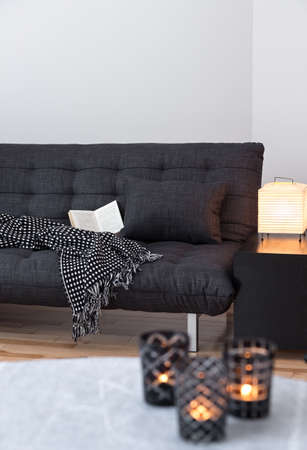 tealight: Cozy lights decorating living room with gray sofa. Stock Photo