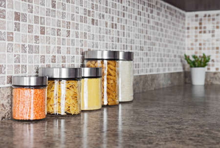stone worktop: Food ingredients in glass jars on a kitchen counter top.