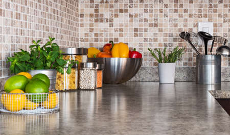 Modern kitchen countertop with food ingredients and green herbs.