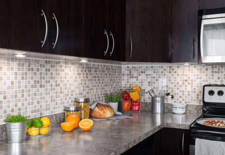 armario cocina: Cocina moderna con los ingredientes alimentarios de colores sobre encimera.