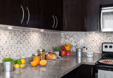 Contemporary kitchen with colorful food ingredients on counter top.